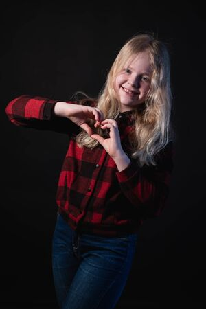 happy schoolgirl posing in studio on a black background - shows hands signs hearts Stock Photo