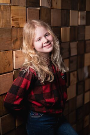portrait of a blonde teen girl near a decorative wall of wooden blocks in studio Stock Photo