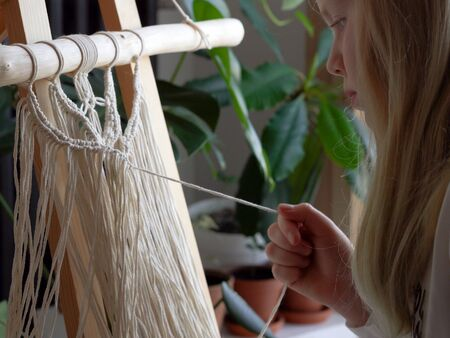 stay at home. work during the quarantine - a girl in the living room mural weaving of the ropes in the macrame technique. Stock Photo