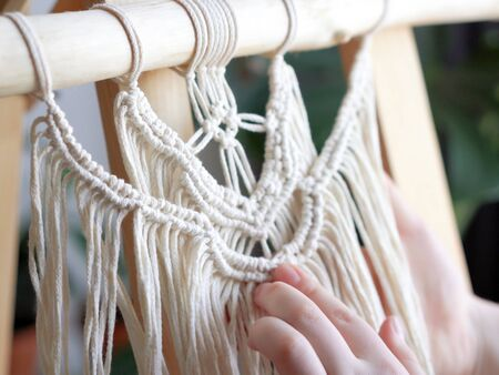 stay at home. work during the quarantine - a girl in the living room mural weaving of the ropes in the macrame technique