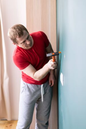 repair and decoration. a man drives a wall plug with a hammer