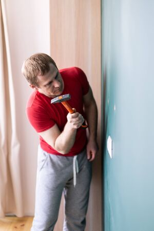 repair and decoration. a man drives a wall plug with a hammer Stock Photo - 146301643