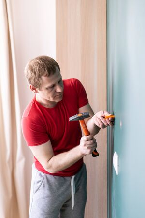 repair and decoration. a man drives a wall plug with a hammer Stock Photo - 146583281