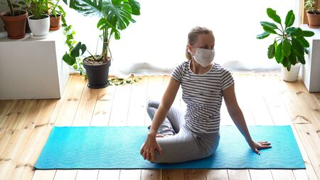stay at home. masked woman doing yoga in the living room during quarantine Stock Photo - 146983643