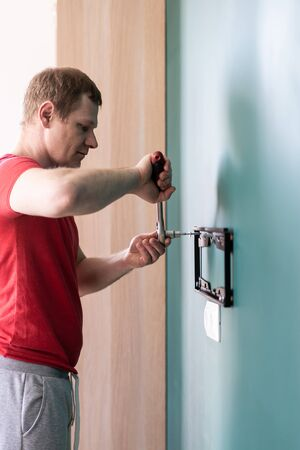 repair and decoration. husband for an hour service. a man attaches a TV mount to a wall. Stock Photo - 146983473