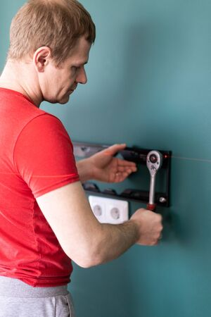 repair and decoration. husband for an hour service. a man attaches a TV mount to a wall. Stock Photo