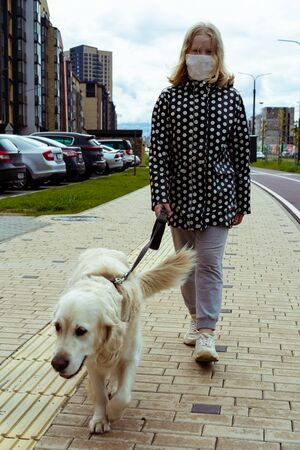 coronavirus pandemic in the city. girl walking a golden retriever dog along empty streets Stock Photo - 149129656