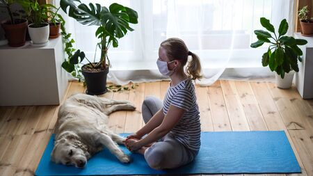 stay at home. woman doing yoga in the living room during quarantine, a large dog is lying nearby.