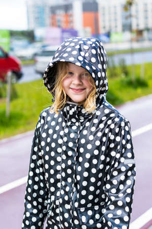portrait of a beautiful teenager girl in a raincoat in the rain