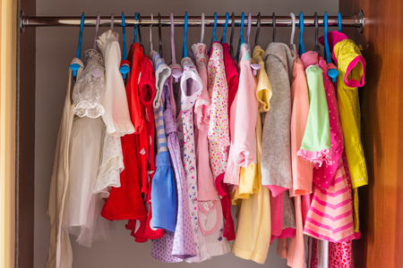 baby wardrobe: Bright colored childrens clothes in the closet Stock Photo