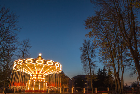 Childrens Carousel at night with night illumination enabled golden light