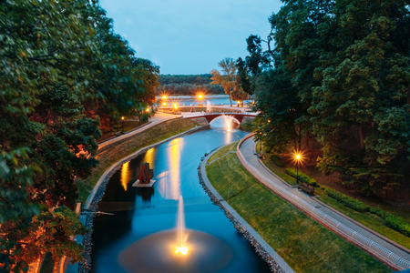 Water canal in the city park with the lights and night illumination over a stone bridge leading to the river Sozh Stock Photo