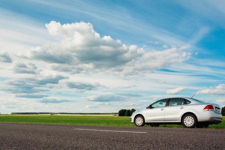 Gomel, Belarus - June 13, 2016: Volkswagen Polo car parked on the side of the road against the beautiful cloudy blue sky and green field in the countryside