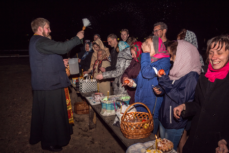 sanctification: Dobrush, Belarus - May 1, 2016: People rejoice that they are sprinkled with holy water. Easter night service Editorial