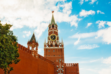 Kremlin wall and Spasskaya tower against a blue sky with clouds