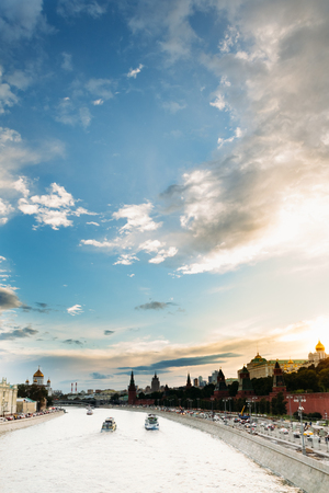 City landscape with the Moscow River with three ships, Kremlin Embankment against the beautiful cloudy sunset sky