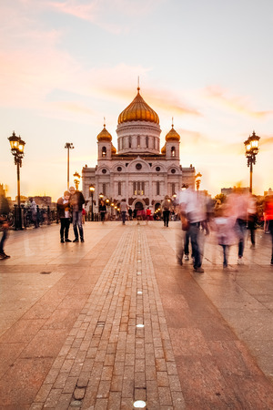Patriarchal bridge with people blurring. Christ the Savior Cathedral at sunset Stock Photo
