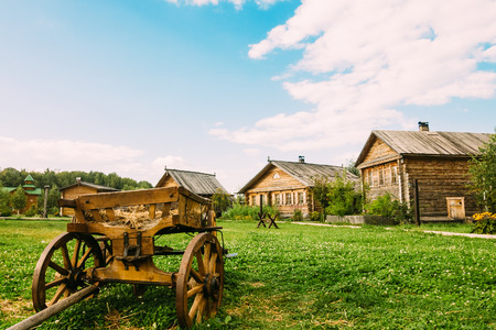 Old wooden cart on the green grass in rural areas. Summer day with a beautiful sky and white cumulus clouds