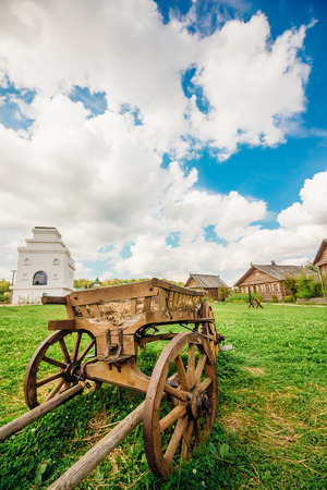 Wooden cart in the foreground, on a background of green grass and beautiful blue sky with white clouds
