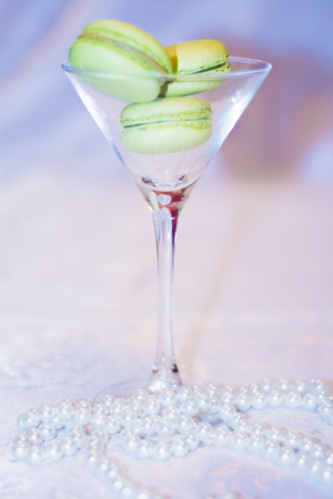 A glass of martini which is a French dessert macaron on a white background Stock Photo