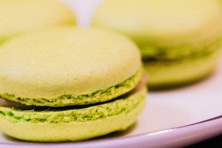 Dessert macarons yellow color on a white plate closeup