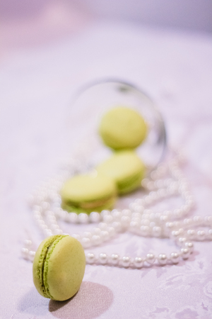 French dessert macarons on the background of pearl beads and glass martini glass in a blur Stock Photo