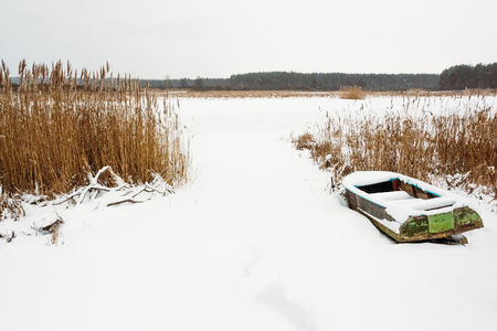 River reeds by the river in winter and an old boat in the snow. Winter