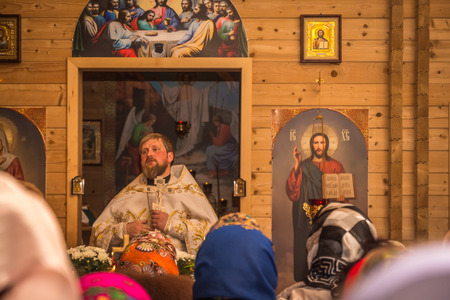 sanctification: Dobrush, Belarus - May 1, 2016: The priest prays to his parishioners during Easter