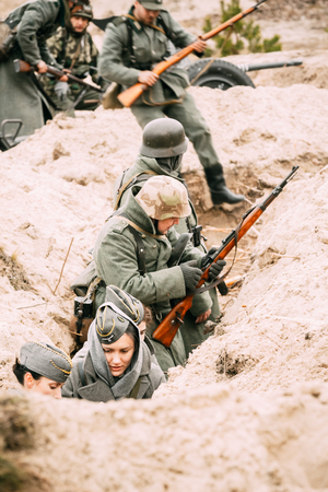 A German soldier in a trench with a rifle. Soldiers occupy the defense. Reconstruction