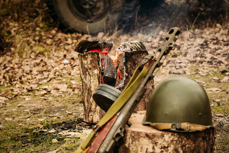 world war ii: Red Army weapons and helmet against the campfire background Stock Photo