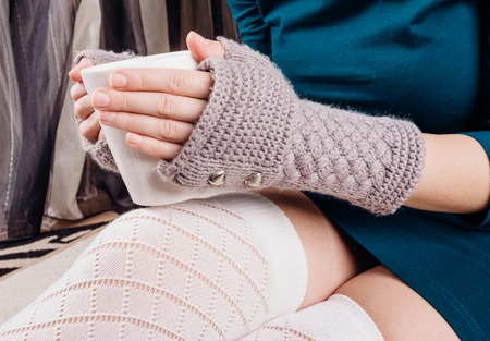 The hands of a young girl in gloves without a finger hold a white cup of tea Stock Photo