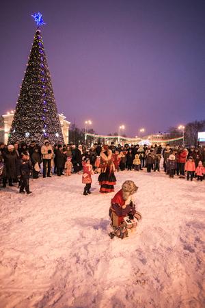 People celebrate Christmas carols near the citys Christmas tree