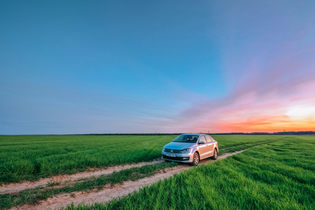 Silver sedan Volkswagen Polo Vento in the field at sunset. Dobru