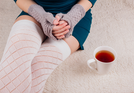 Legs of a young girl in a green dress with gloves without fingers sitting on a rug next to a cup of tea