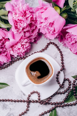 Black coffee with pink peonies on a concrete light background
