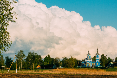 Orthodox church in a village against a backdrop of cumulus clouds. Krasnyy Partizan, Dobrush District, Gomel Region, Belarus. Stock Photo