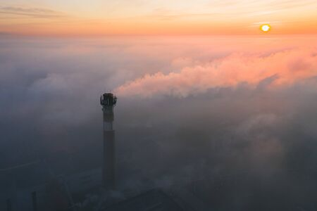 Factory chimney with smoke in the fog covering the whole city at sunrise Stock Photo