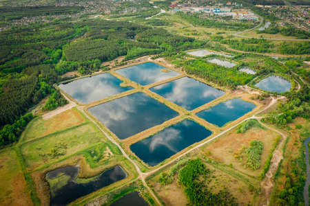 Artificial pond, for maintenance and purification of water from sewage. Water storage for purification from impurities. Urban water treatment in clusters. Reflections sky in mirror water. Aerial view