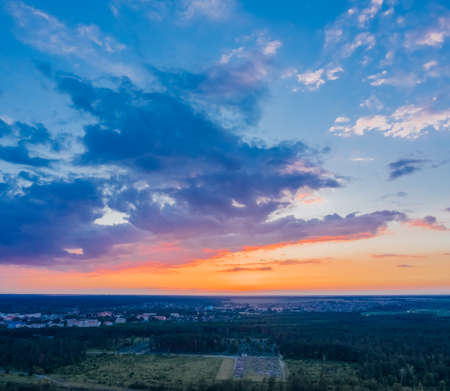 Sunset sky with clouds. The sun shines on the clouds after sunset. Beautiful nature with glam and forest. Aerial view 免版税图像