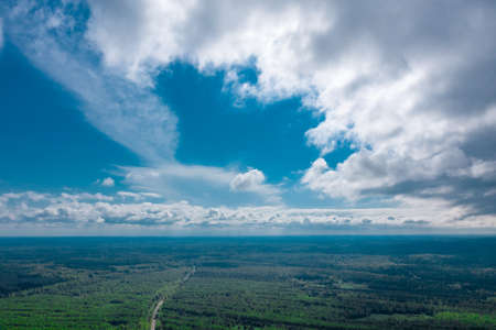 A dramatic blue sky with clouds over endless forest expanses. Aerial view