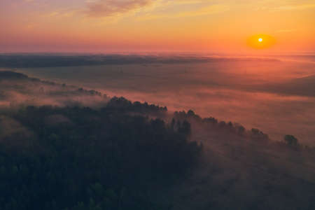 Beautiful red dawn on a summer morning with fog in the forest and fields. View from above 免版税图像