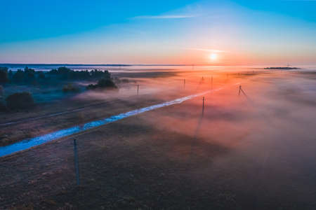 Beautiful bright sunrise in the fields of Belarus with fogs on a summer morning. View from above