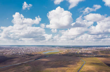 Landscape from a height of flight overlooking rural fields with a beautiful cloudy blue sky.