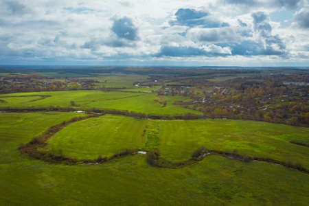Green fields and rivers under a picturesque sky with clouds. Autumn landscape from above view