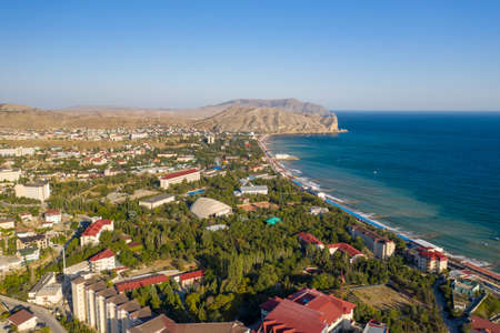 The resort town of Sudak in Crimea from a height view of the coastline with beaches and mountains in the distance