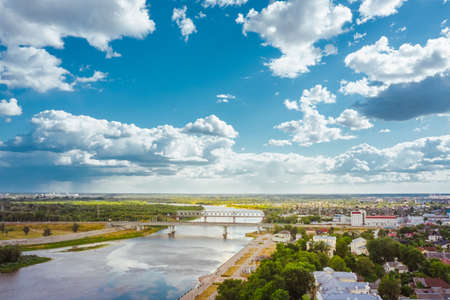 Cityscape with a bridge over the river a bright day with a blue sky and clouds over the city. Many green areas and forests. Aerial view