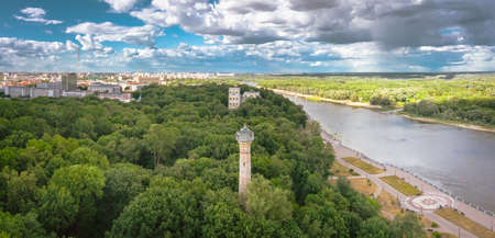 City panorama public park with a large green area near the river an old lighthouse in the trees a blue sky with cumulus clouds on the landscape. Aerial view 免版税图像