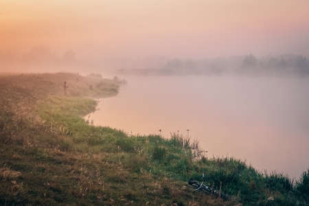 Fishermen in the morning in the fog on the lake fish. Summer morning