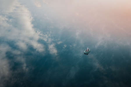 Lonely fisherman in a boat among the lake reflection of sky and clouds in smooth water. Calm and relaxation hobby man with fishing rod fishing early in the morning. Aerial view