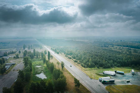 Atmospheric landscape with a transport highway in the fog, with trucks on the road, pine trees on the left and rain clouds in the sky. Aerial view